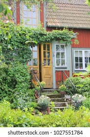 Wooden red cottage entrance with many windows and door ajar in the countryside of Sweden, surrounded by beautiful greenery at summer time.
