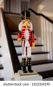 Wooden red Nutcracker Christmas Soldier perched on a farmhouse staircase newel post