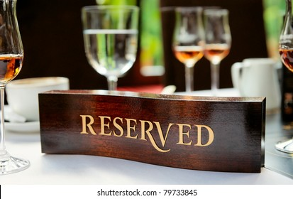 Wooden reserved plate on an arranged restaurant table