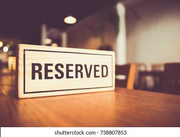 wooden reserved sign with capital letters on dining table in restaurant, retro tone