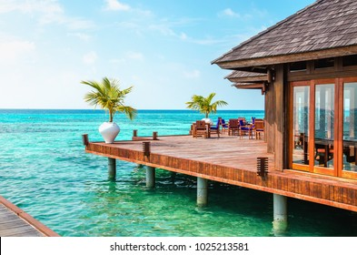 A wooden restaurant on the water against the backdrop of the azure waters of the Indian Ocean, Maldives