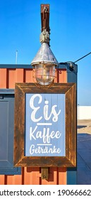 Wooden restaurant sign on the beach. Letter with Kaffee Eis Getränke means Coffee Ice Drinks. - Shutterstock ID 1906666204