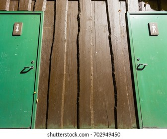 Wooden restroom building outside architecture with green doors and signs for men and women