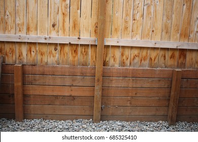 Wooden retaining wall with fence above it.