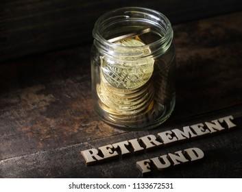 Wooden RETIREMENT FUND text with golden coins in a mason jar on dark wood background