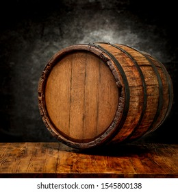 Wooden retro barrel on table and free space for your decoration. Black worn wall background.