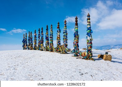 Wooden ritual pillars with colorful ribbons on cape Burkhan, Lake Baikal, Olkhon Island, Siberia, Russia