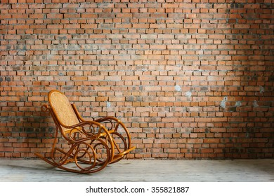 Wooden rocking chair against old brick wall background interior