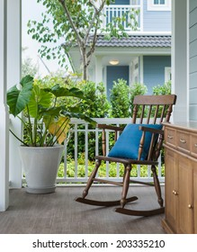 wooden rocking chair on front porch with pillow and planter