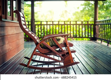 Wooden rocking chair on front porch with pillow , Rocking chair in grunge house