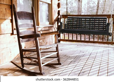 Wooden rocking chair on a porch deck of a log cabin with a wooden swing blurred in the background