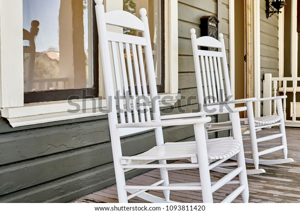 Wooden rocking chairs on front porch of a victoran home under restoration