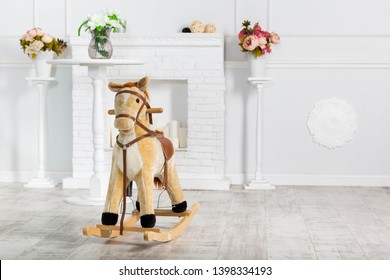 Wooden Rocking Horse. The toy stands on the background of a decorative fireplace and light blue wall and stands with flowers
