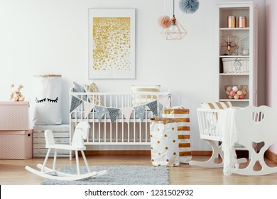 Wooden rocking horse, white and gold paper bags and white wooden crib in cozy baby nursery with painting on the wall