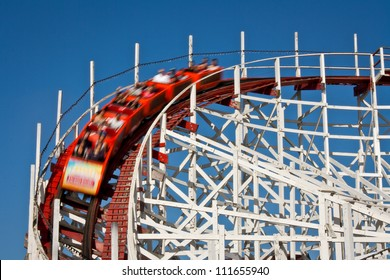 A wooden rollercoaster with people (blurred motion).