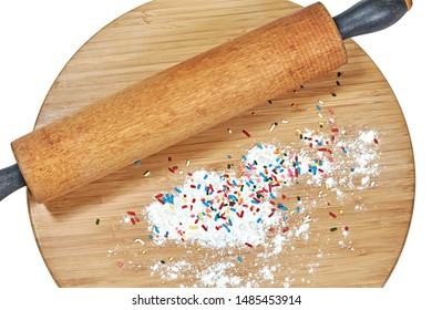 A wooden rolling pin on a bamboo cutting board with white flour and multi-colored sprinkles on the board isolated on white