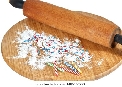 A wooden rolling pin on a bamboo cutting board with white flour and red, white and blue sprinkles and birthday candles on the board isolated on white