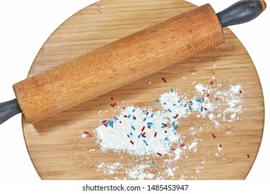 A wooden rolling pin on a bamboo cutting board with white flour and red, white and blue sprinkles on the board isolated on white
