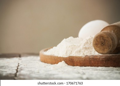 Wooden rolling pin with remnants of flour in a rustic table
