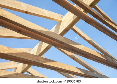 wooden roof with rafter style framing against a blue sky - Roof Rafter