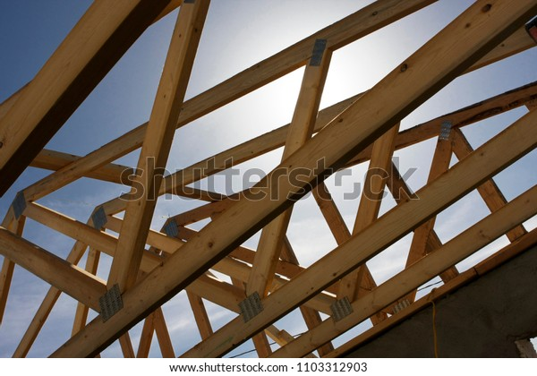 Wooden roof trusses in construction of new house looking up at an angle
