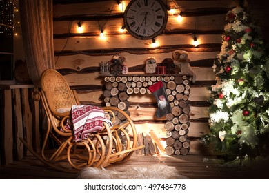Wooden room in rustic house with wooden fireplace, decorated Christmas tree and rocking chair