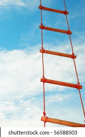 Wooden rope ladder on a blue sky background