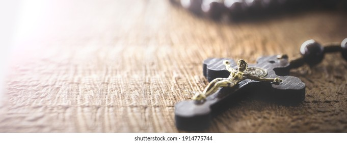 wooden rosary radiated by divine light, concept of faith and spirituality, copy space