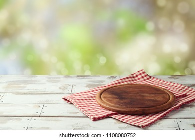 Wooden round board with checked tablecloth on table over bokeh nature background