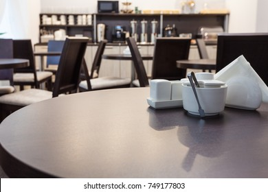 Wooden round table and sugar bowl, napkins, salt and pepper in modern cafe with furniture of kitchen on the background. Interior