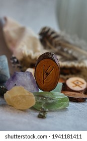 wooden rune of the fehu among the crystals