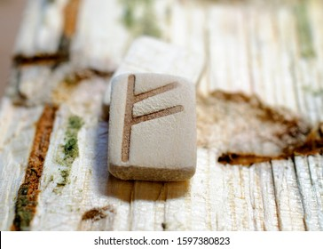 Wooden rune Fehu close-up on a wooden background. Soft focus