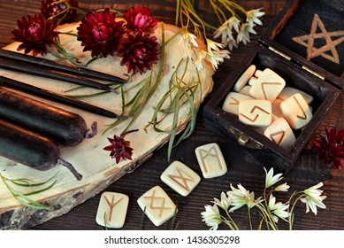 Wooden runes and black candles on witch table. Wicca, esoteric, divination and occult concept with vintage magic objects for mystic rituals, Halloween background
