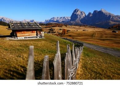 Wooden rural farmer's shed (hut) and a wooden fence in Seiser Alm meadow in the Dolomites, North Italy, Sudtirol (Trentino / Alto Adige). Scenic autumn view of a big valley in the Alps Mountains