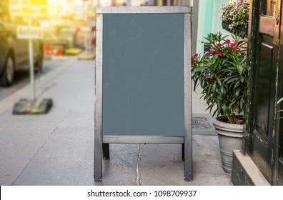 Wooden rustic blackboard in front of restaurant entrance