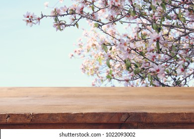 wooden rustic table in front of spring cherry blossoms tree. product display and picnic concept