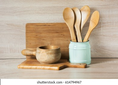 Wooden rustic and vintage crockery, tableware, utensils and stuff on wooden table-top. Kitchen still life as background for design. Image with copy space.