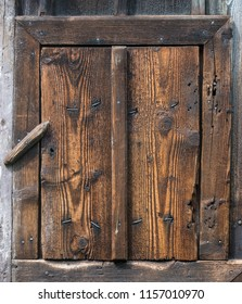 Wooden rustic wicket closed by a revolving lock. Small rural door from brown roughly textured wood with nails and knots. Village background of vintage planks, frame from laths and safety catch.