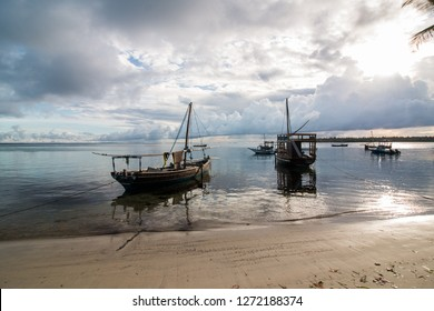 Wooden sailboats on the water at the beach at sunrise in Mafia Island, Tanzania, with cloudy sky and calm water.