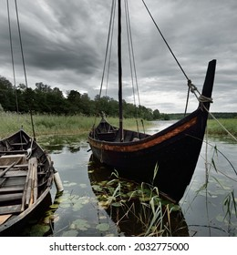 Wooden sailing boats moored to a pier. Birka, Björkö island, lake Mälaren, Sweden. Atmospheric landscape. Travel destinations, landmarks, sightseeing, history, historical reenactment, viking age