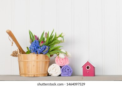 Wooden sauna bucket with flowers and towels