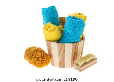 Wooden sauna bucket with sponge brush and towels