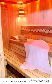 wooden sauna interior with towel and bucket