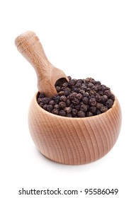 Wooden scoop in bowl full of black peppercorn isolated on white
