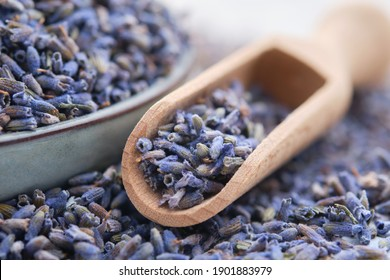 Wooden scoop of dry lavender flowers and blue plate of dried lavender. close up. Selective focus.