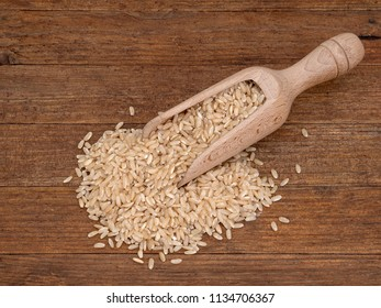Wooden scoop with long grain brown rice on rustic wooden board. With copyspace.