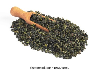 Wooden scoop over tieguanyin oolong green tea leaves on white background