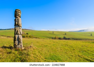 Wooden sculpture on meadow in autumn landscape of Beskid Niski Mountains, Poland