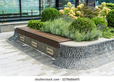 Wooden seat near a decorative flower bed laid out with a stone