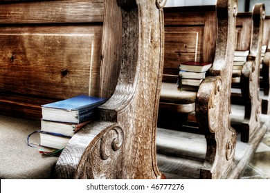 wooden seats in an antique church with books on it